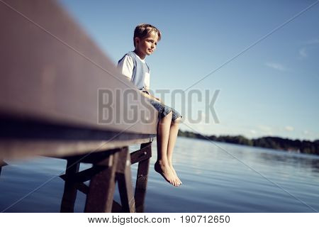 Boy with barefoot legs and feet dangling from pier by lake on summer vacation