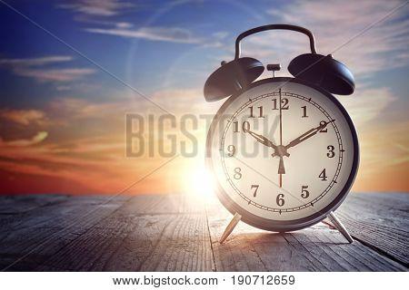 Alarm clock on wood table at sunset