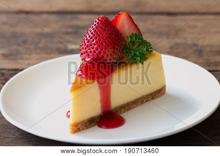 Homemade New York cheesecake on white plate decorated by strawberry,parsley and strawberry sauce. Homemade New York cheesecake on white plate decorated by strawberry, parsley and strawberry sauce. Moist and smooth classic baked cheesecake. Copy space back