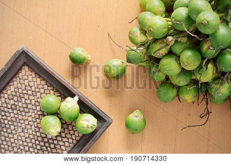 betel nut is dry and a tray on wooden floor.