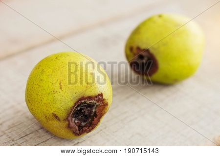 Pear with a bruise that is going to rot on wooden.
