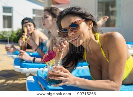 Three Beautiful girls in swimwear and sun glasses are drinking cocktails through a straw while sunbathing on the chaise longue near the pool. One girl is smiling and looking at camera