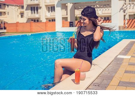 portrait of young sexy girl relaxing at the edge of the swimming pool., wearing swimsuit and drinking cocktails during vacation. Pool party