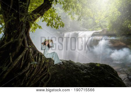 Vietnamese woman sits beneath a beautiful waterfall tree with a happy smile.