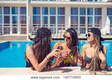 Party at smimming pool. Group of cheerful friends girls at the edge of the swimming pool drinking cocktails and laughing