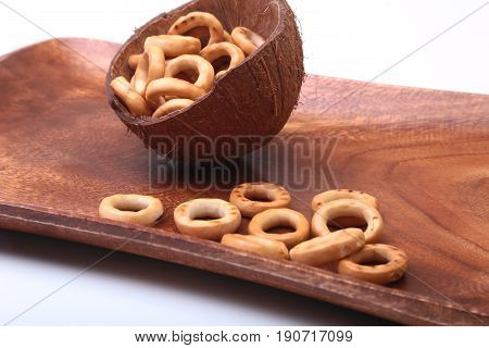Salty Mini Pretzels with Salt in a Bowl, small bagel - homemade organic snack for beer in wood bowl isolated white background.