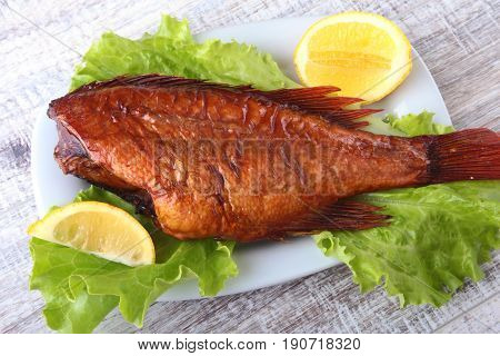 Smoked fish and lemon on green lettuce leaves on Wooden cutting board isolated on white background