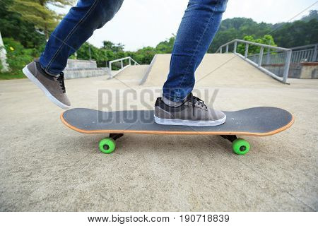 closeup of skateboarder legs skateboarding at skatepark