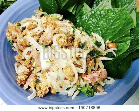 Thai Cuisine and Food Thai Traditional Yum Nam or Spicy Pork Skin Salad with Sour Preserved Pork and Curried Rice Croquettes Served with Betel Leaves.