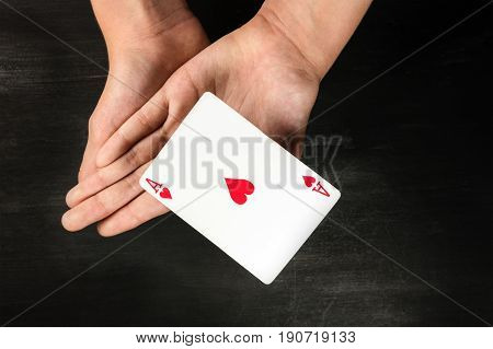 A photo of a card levitating above the hands of a girl, on a black background with a place for text. A simple magic trick performed by a child