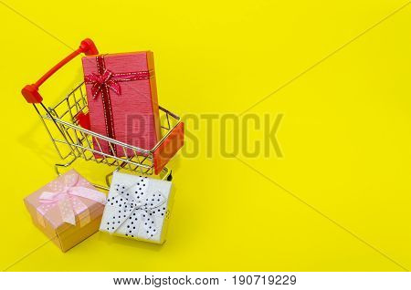 mini colorful gifts box in mini supermarket shopping cart on yellow background holiday sale and online shopping concept selective focus copy space