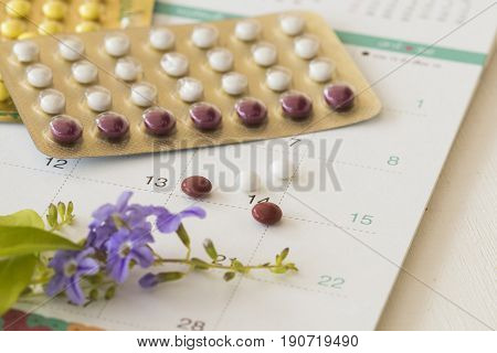 birth control pill of baby for woman and calendar on white