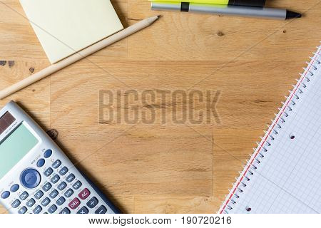 Work desk with note pad calculator and biro on wooden table from above