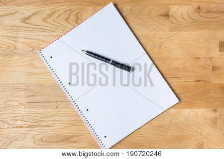 Work desk with note pad and biro on wooden table from above
