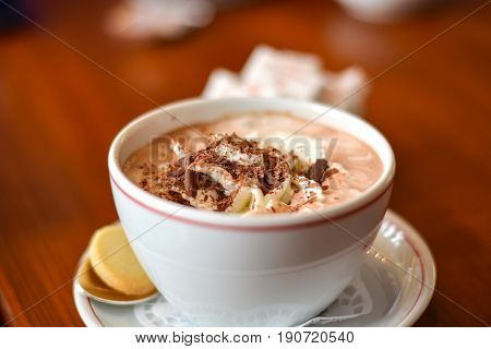 Hot chocolate with cream and chocolate grating on top in a cup