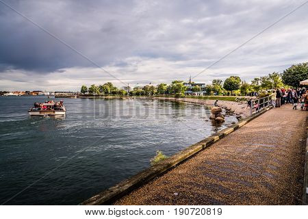 Copenhagen Denmark - August 10 2016. Tourists visiting the Little Mermaid. The Little Mermaid is a bronze statue by Edvard Eriksen. The sculpture is displayed on a rock by the waterside in Copenhagen
