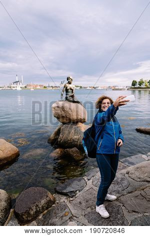 Copenhagen Denmark - August 10 2016. Tourist taking a selfie in the Little Mermaid. The Little Mermaid is a bronze statue by Edvard Eriksen. The sculpture is displayed on a rock by the waterside in Copenhagen