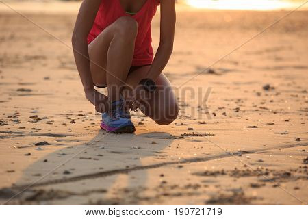 Healthy lifestyle young fitness woman runner tying shoelace at sunny beach