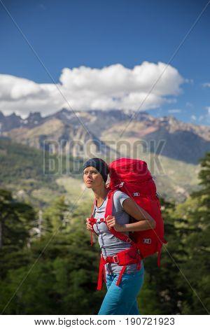 Pretty, female hiker in high mountains admiring the vistas, setting for a long trek