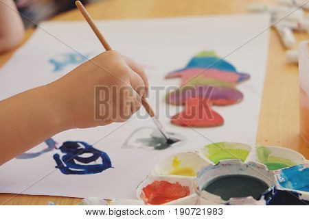Kid painting on white paper, education concept