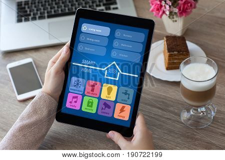 woman hands holding tablet computer PC with app smart home on table in cafe