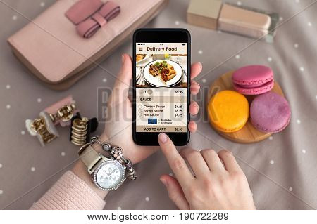 female hand with jewelry holding phone with app delivery food on screen
