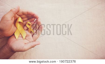 yellow gold ribbons on hands Sarcoma Awareness Bone cancer Liver cancer Bladder Cancer childhood cancer awareness