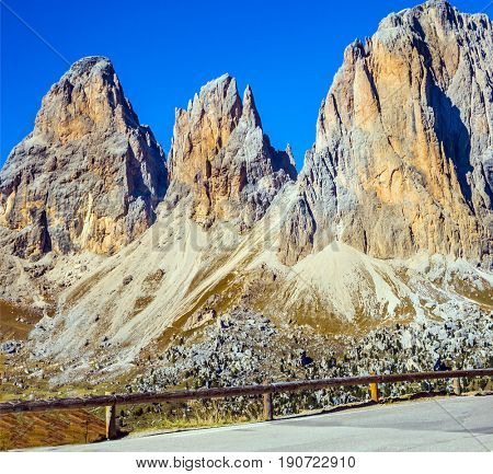 Three dizzy dolomite peaks. Picturesque road through the Sella Pass, Dolomites. The concept of extreme and ecological tourism