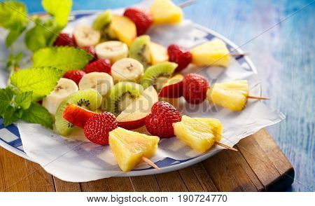 Fresh Fruit skewers, healthy and delicious dessert  on a blue wooden table