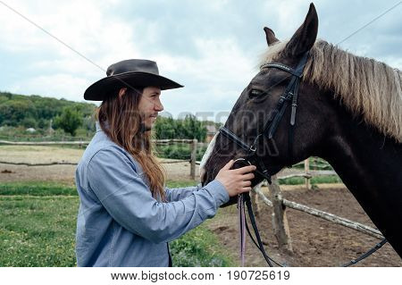Young Man With Long Hair In Hat Holding Horse's Muzzle On Countryside And Looking At Horse