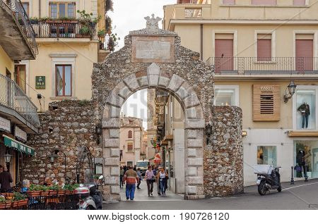 Locals and tourists pass through the Messina Gate (Porta Messina) at the northern end of Corso Umberto - Taormina, Sicily, Italy, 22 October 2011