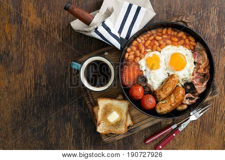 Full English breakfast with sausages bacon fried eggs beans toast and cup of coffee on wooden table with copy space top view