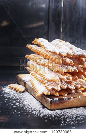 Italian Frappe or chiacchiere - typical Italian carnival fritters dusted with powdered sugar on old black wooden table. With free text space.