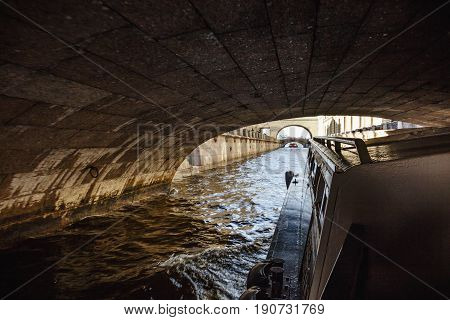 View floating under a bridge in one of the canals or rivers of St. Petersburg by boat