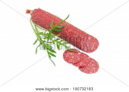 Partly sliced salami and fresh twig of the arugula on a light background