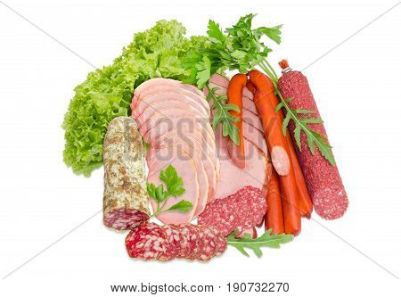 Sliced boiled smoked pork loin and ham partly sliced two different salami and hunting sausages with arugula lettuce and parsley on a light background