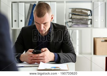 Handsome Thoughtful Businessman Look At Cellphone In Hand