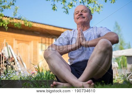 Senior man with mustache with namaste sitting.Concept of calm and meditation.