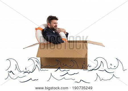 Afraid businessman with cardboard and lifebelt in the ocean