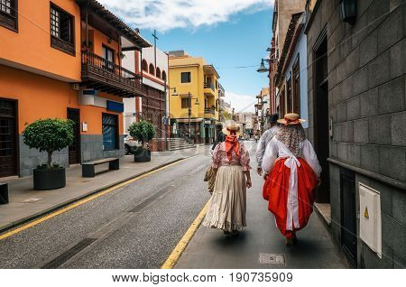 A group of locals in Canarian traditional clothes walk along the street of Puerto de la Cruz with colorful houses. Celebration of the Day of Canary Islands. View from the back. Tenerife 30 may Spain