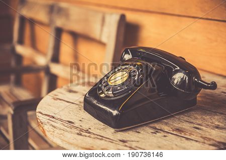 old telephone black color on wood table. classic retro vintage style rotary dial calling telephone type number.