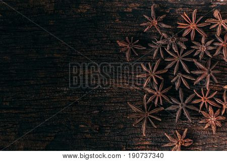 Anise stars on wood background for food seasoning.