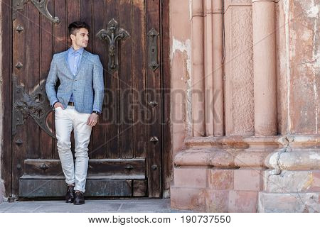 Positive man is leaning against solid wooden forged door. He looking aside with wistfulness. Copy space on right side