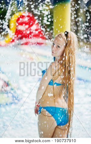 Portrait Of A Beautiful Girl Wearing Blue Bikini In A Pool Posing With The Water Sprinkling Above He