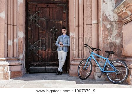 Happy relaxed man is standing near solid wooden door and fixing cuffs. He locating nearby blue bicycle
