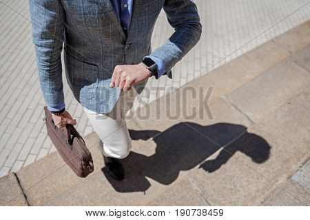 Elegant man is walking up stairs and checking time on modern smartwatch. He carrying brown bag. Top view