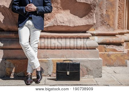 Elegant man is standing near building. Black leather suitcase locating near legs in polished shoes