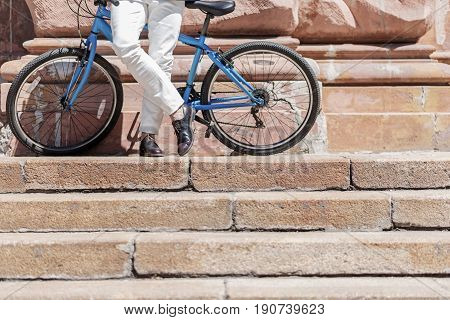 Elegant businessman is leaning against bicycle. Focus on legs in leather shoes. Close up