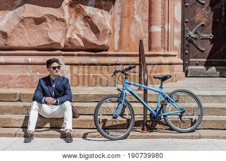 Joyful man wearing sunglasses is sitting on rung near bicycle, leaned against iron banister. He looking aside with light smile