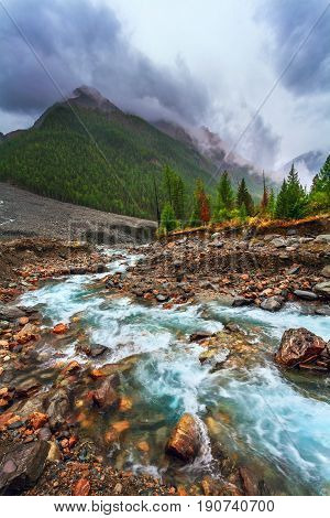 Landscape with the wild nature in rainy weather. On a background the mountain and the dramatic sky are located. In the foreground the rough blue river flows to the horizon.